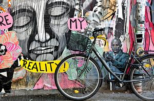 Fiets tegen muur met Berlijnse graffiti.