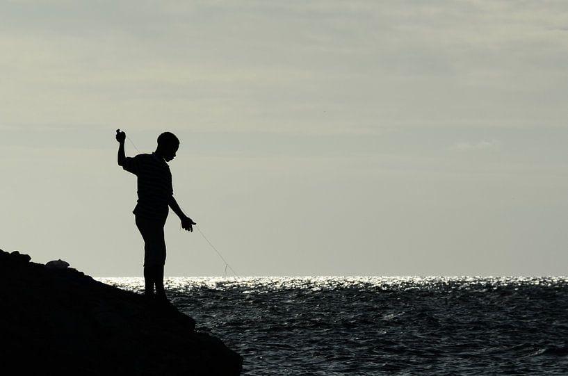 Jongen op rotsen aan het vissen van Christopher Lewis