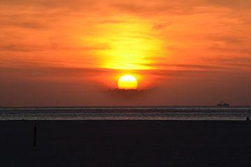zonsondergang aan de kust van Texel met een vissersboot aan de horizon van tiny brok