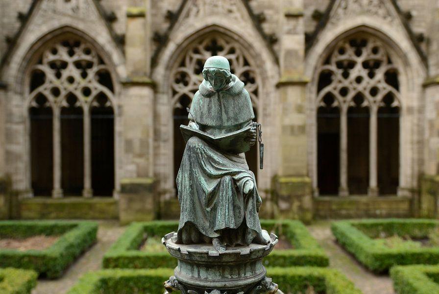 Bronzen beeldje van een schrijvende monnik in de kloostertuin van de Domkerk in Utrecht