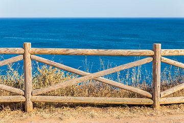Houten hek aan kust bij blauwe zee in Portugal van Ben Schonewille