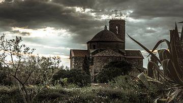 De oude kerk van Garriguella, Spanje. Opeen bruin/groene manier weergegeven. Bij ondergaande zon. van Fred Louwen