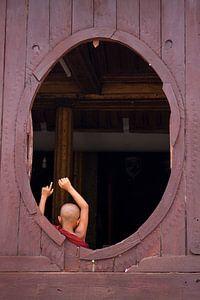 Jonge monnik in ovaal venster van
