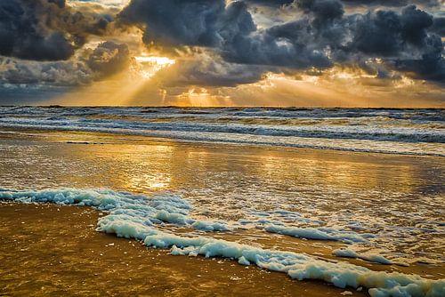 Zonsondergang boven zee tijdens bewolkte lucht.