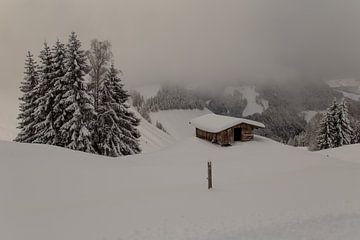Cabane de montagne dans la neige vue du sommet nuageux sur Guido Akster