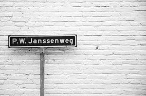 'P.W. Janssenweg' straatnaambord in Jubbega, zwart-wit foto.