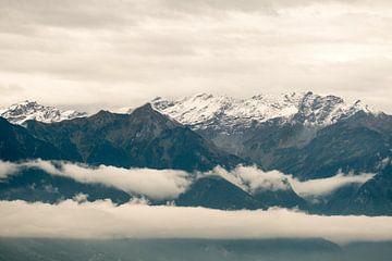 Wolken tussen de besneeuwde bergtoppen. van Idema Media