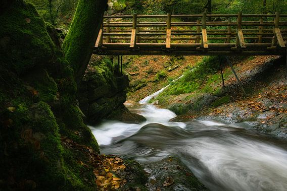 Snelstromende rivier onder een houten brug.
