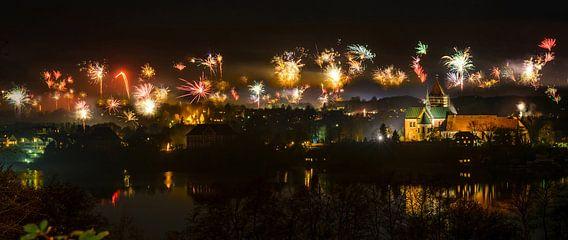 Nieuwjaarsvuurwerk boven de oude stad Ratzeburg bij nacht met verlichte kathedraal en reflecties in