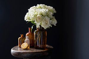 Stilleben mit weißen Rosen in braunen Flaschen und Zitrone
