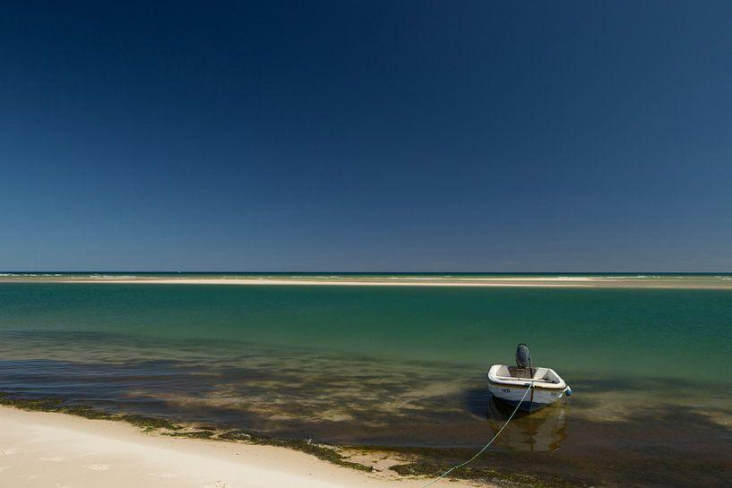 Helderwit strand met blauwe zee en lucht een boot in Portugal van Arjan Groot
