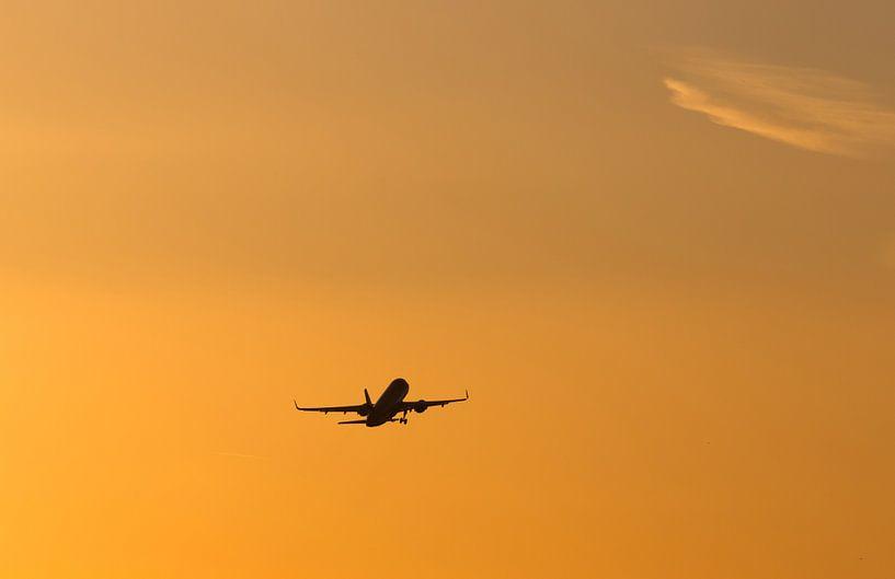 Un avion décolle au coucher du soleil sur Frank Herrmann