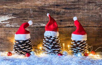 Kerstversiering met dennenappels versierd met rode kerstmutsen over sneeuw met helder licht van Alex Winter
