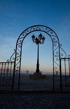 Sierlijk hek en lantaarn in de schemering van Edith van Aken