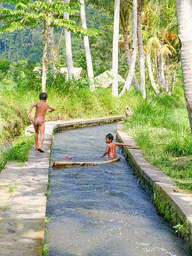 Twee kindjes spelen in de rivier in Bali van Petra Brouwer
