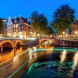 Lichstrepen op de Amsterdamse grachten bij nacht van Arjan Almekinders