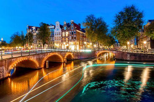 Lichstrepen op de Amsterdamse grachten bij nacht van