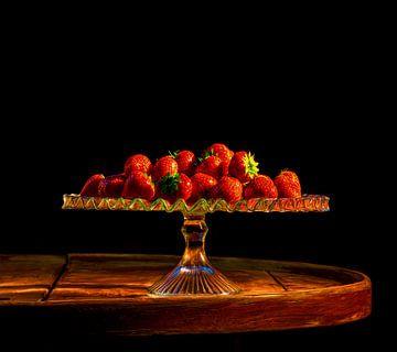 Aardbeien op glazen schaal en oude tafel zwarte achtergrond van