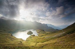 sunlight through clouds over alpine lake