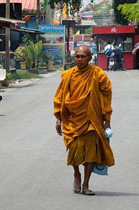 Monnik in gewaad loopt over straat in Thailand