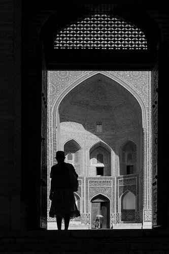 Vrouw in deuropening madrassa Bukhara van