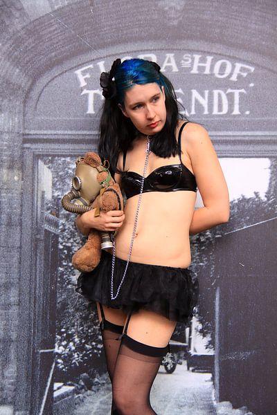 Frau mit sexy Fetischkleidung hält einen Teddybär von Bobsphotography
