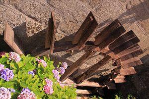 Altes hölzernes Wasserrad mit Blumen