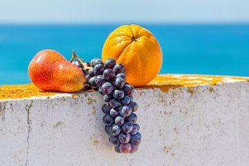 Frisches Obst liegt auf weißer Wand vor blauem Meer von Ben Schonewille