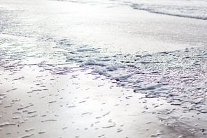 Strand met zeeschuim bij tegenlicht