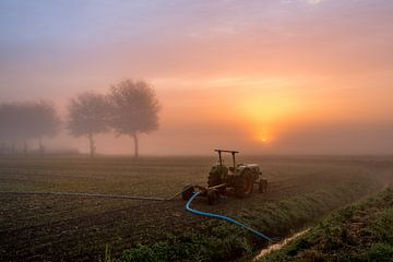 Tractor pompt water uit de sloot tijdens mistige zonsopkomst van Moetwil en van Dijk - Fotografie