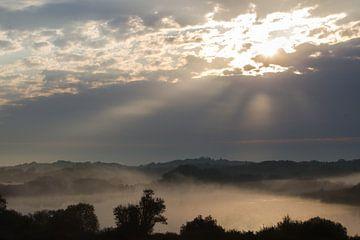 Zon door wolken boven mist duinlandschap van Menno van Duijn