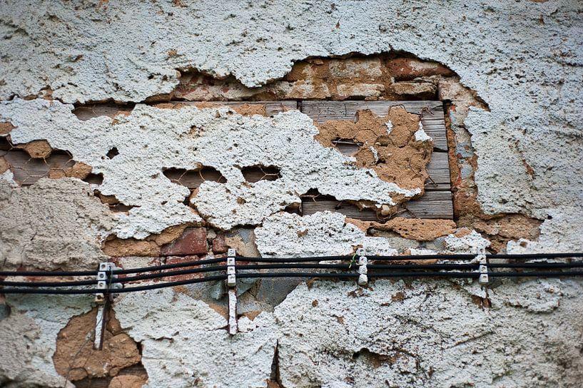 Vlakvulling: oud pleisterwerk valt van de muur. van Nic Limper