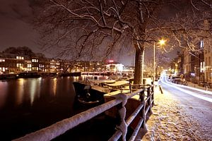 Besneeuwd Amsterdam bij nacht in Nederland