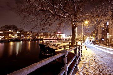 Besneeuwd Amsterdam bij nacht in Nederland van