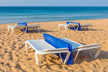 Ligbedden op leeg Portugees strand met blauwe zee van