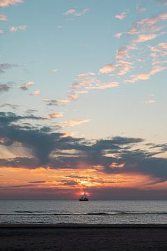 Zonsondergang boven de zee met boot. van Amber den Oudsten