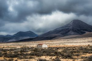 Klein onafgebouwd huisje op een vlakte in een dal met zware lucht.