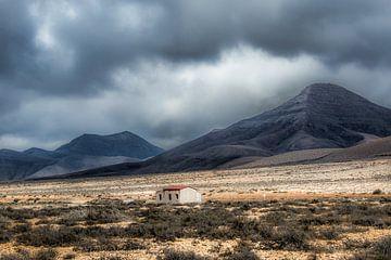 Klein onafgebouwd huisje op een vlakte in een dal met zware lucht. sur Harrie Muis