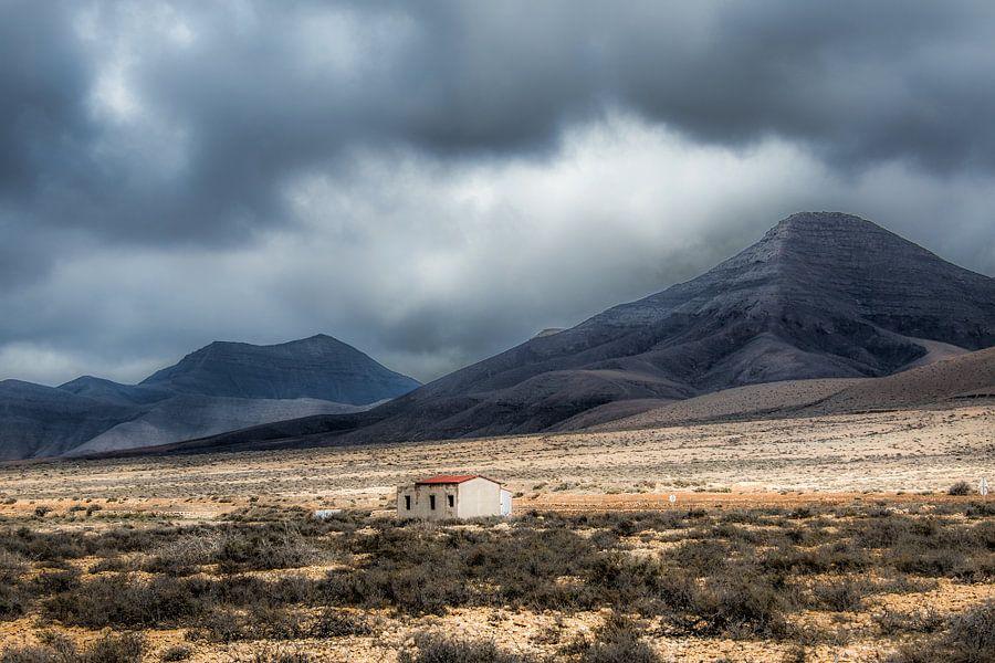 Klein onafgebouwd huisje op een vlakte in een dal met zware lucht. van Harrie Muis