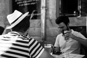 2 mannen genieten van een biertje op het terras van