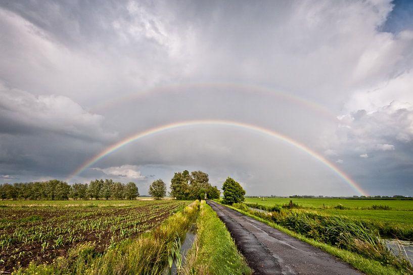 Regenboog over de polder. van John Verbruggen