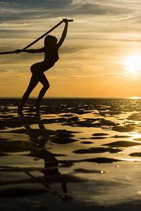 Artistiek naakt met een touw op de waddenzee bij zonsondergang