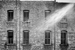 Zonnestraal schiet voor een oud gebouw van