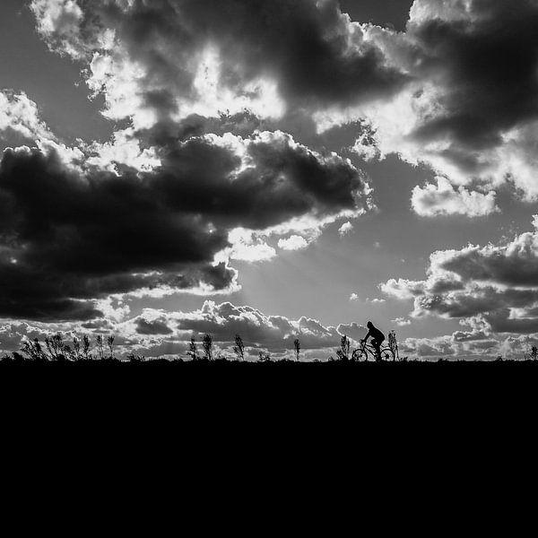 Silhouette van een fietser tegen een mooie wolkenlucht