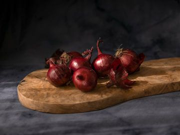Stilleben von roten Zwiebeln auf einer Holzbohle mit dunklem Hintergrund von Wendy Verlaan