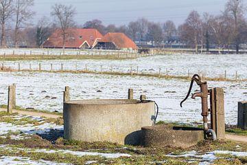 Waterpomp en waterput in winters landschap met sneeuw  van Ben Schonewille