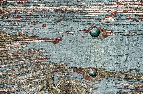 Verweerde plank met afbladderende verf van