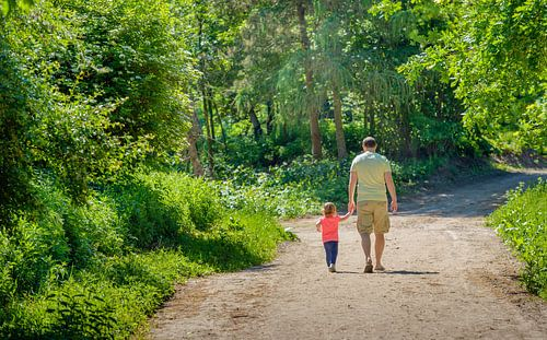 Man wandelt met kind op bospad