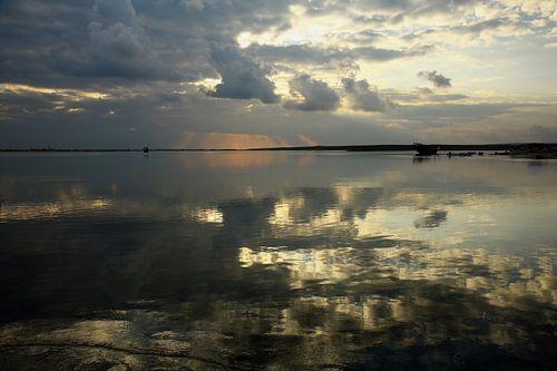 Reflecties in het water bij zonsopkomst in Oman