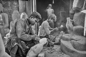 Beeldhouwer aan het werk zittend tussen Budha beelden in Mandelay aan de Marble Road van